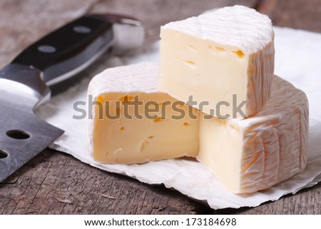 brie cheese on old wooden table and knife closeup  - stock photo