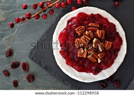 Brie topped with cranberries and pecans, above view on slate background