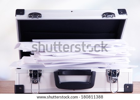 Briefcase full of papers, on wooden table, on light background