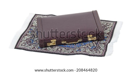 Briefcase on a flying carpet with intricate patterns of bright colors - path included - stock photo