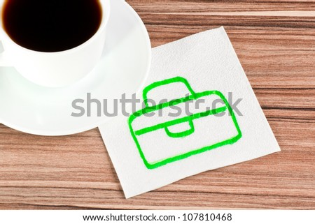Briefcase on a napkin and cup of coffee - stock photo