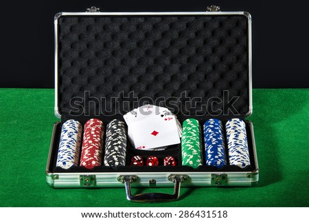 Briefcase poker with cards and dice betting - stock photo