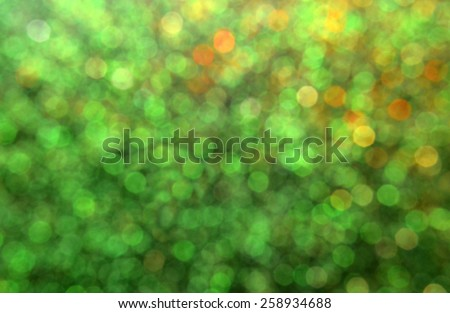 Bright and abstract blurred green background with golden shimmering glitter - stock photo