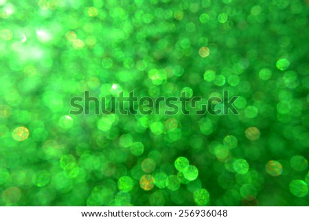 Bright and abstract blurred green background with shimmering glitter