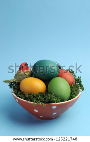 Bright and cheerful Easter rainbow color eggs in orange polka dot bowl against a blue background. Vertical portrait orientation. - stock photo