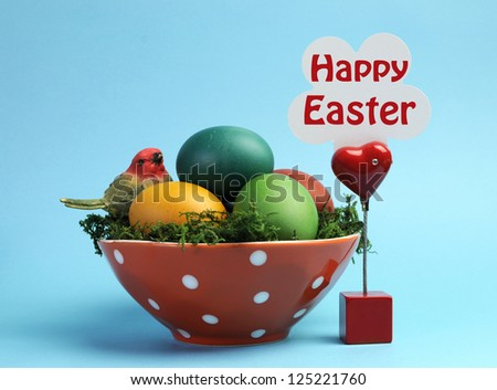 Bright and cheerful Easter still life with rainbow color eggs in orange polka dot bowl against a blue background, with Happy Easter sign. - stock photo