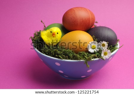 Bright and cheerful Happy Easter still life with rainbow color eggs in blue polka dot bowl against a pink background. - stock photo