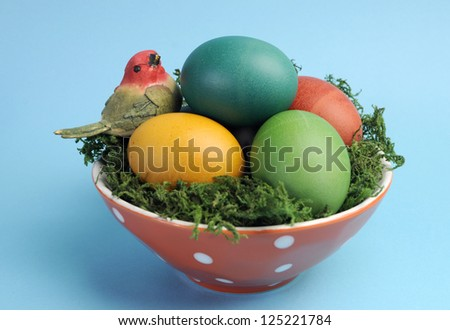Bright and cheerful Happy Easter still life with rainbow color eggs in orange polka dot bowl against a blue background. - stock photo