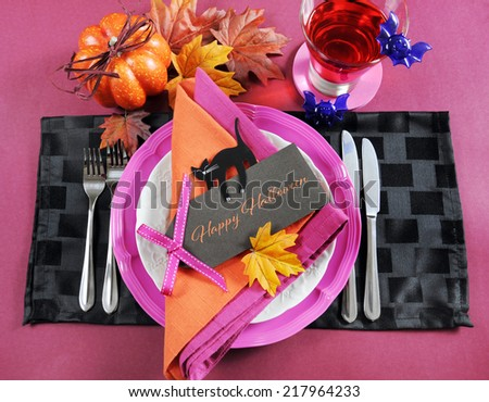 Bright and colorful pink, orange and black modern Happy Halloween table place setting with greeting tag text message. .