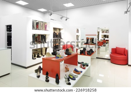 bright and fashionable interior of shoe store in modern mall - stock photo