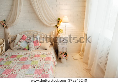Bright and fresh bedroom decorated with a bouquet of flowers. - stock photo