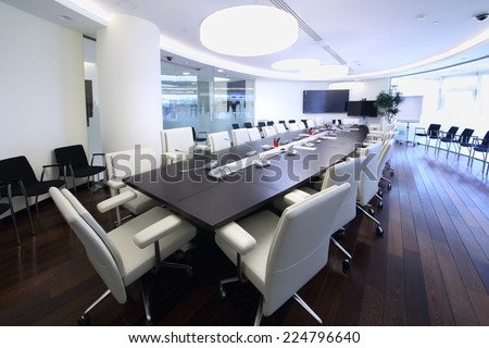 Bright and spacious conference hall with long negotiating table and white chairs in office
