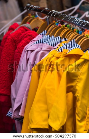 Bright autumn raincoats hanging at a fashion store