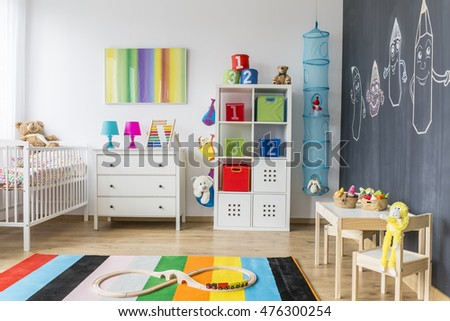 Bright baby room full of colours with white furniture and toys