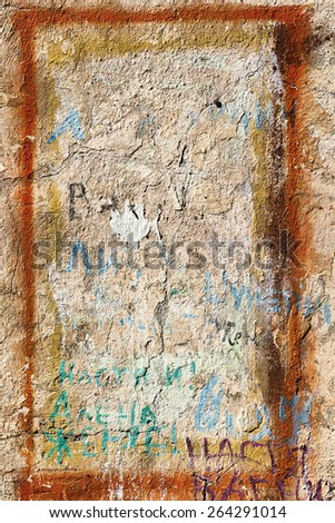 Bright background of the old wall in shades of yellow, spoiled different inscriptions with scratches and cracks. Textured background for your concept or project. Great background or texture. - stock photo