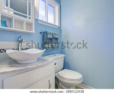 Bright bathroom with blue walls and marble counter.