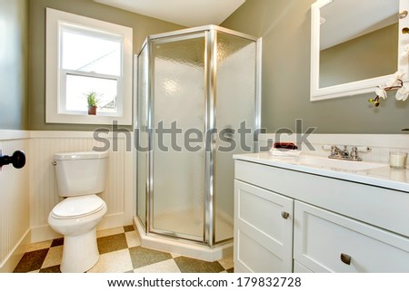 Bright bathroom with window. Olive walls blend perfectly with white cabinets, white toilet and glass door shower - stock photo