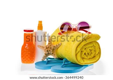 Bright beach accessories isolated on white: flip-flops, sunscreen, sunglasses, towel, starfish, juice. - stock photo