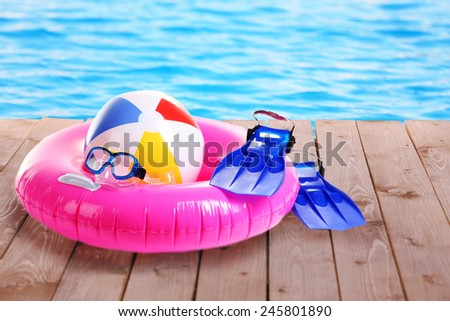Bright beach accessories on pool background - stock photo