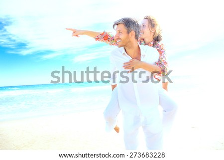 bright beach couple finger outstretched - stock photo
