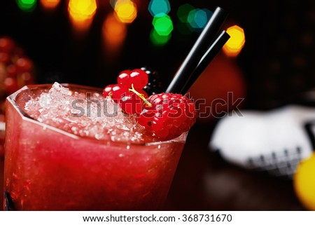 bright beautiful and tasty cocktail or lemonade with a cap of frozen ice and fresh berries on the bar with a nice bokeh of the disco light. soft focus. - stock photo
