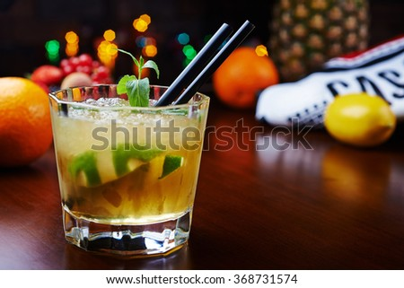 bright beautiful and tasty mint cocktail or lemonade with a  fresh berries and fruits on the bar with a nice bokeh of the disco light. soft focus. - stock photo