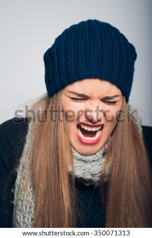 bright beautiful girl angry shouts, studio photo isolated on a gray background