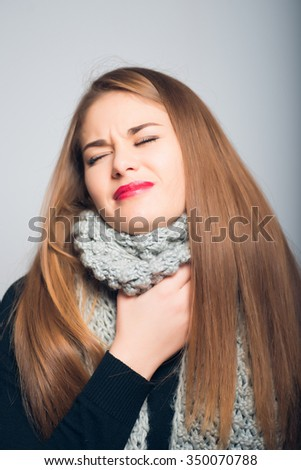 bright beautiful girl has caught a cold and sore throat, Christmas and New Year concept, studio photo isolated on a gray background - stock photo