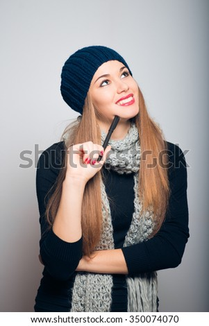 bright beautiful girl thinking with a pen, Christmas and New Year concept, studio photo isolated on a gray background - stock photo