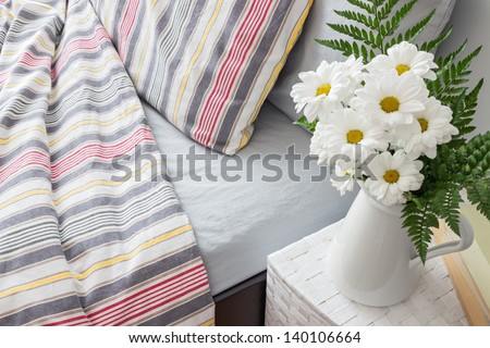 Bright bedroom decorated with a bouquet of white flowers. - stock photo