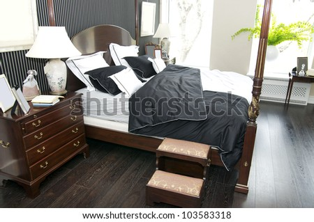 Bright bedroom with a queen size bed and cupboard - stock photo