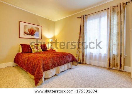 Bright bedroom with beige carpet floor and yellow walls. Red bedding and red frame wall picture accomplish  design - stock photo