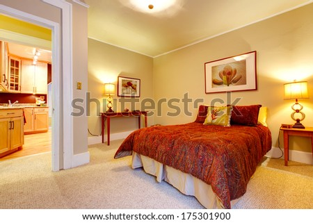 Bright bedroom with beige carpet floor and yellow walls. Red bedding, red frame wall picture and tables accomplish  design - stock photo