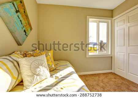 Bright bedroom with beige walls, carpet and good lighting.