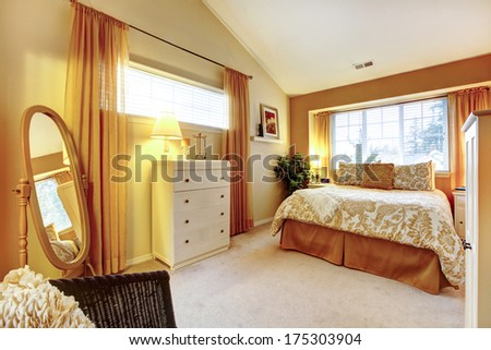 Bright bedroom with high vaulted ceiling. Orange and beige bedding naturally matching with orange wall. Room decorated with green tree and old style mirror. - stock photo