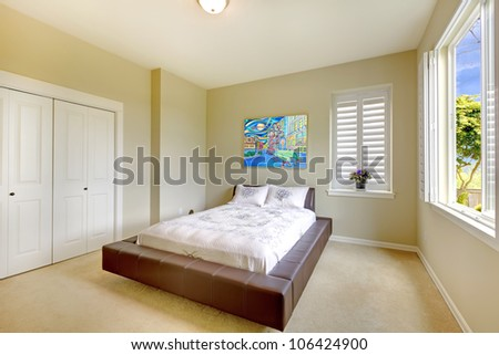 Bright bedroom with modern brown bed and art