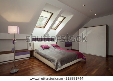 Bright bedroom with wooden floor and violet additions - stock photo