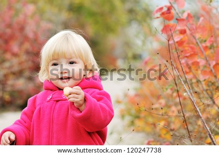 bright blonde baby girl walking in fall park - stock photo