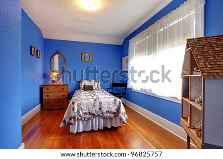 Bright blue kids bedroom in old English style with cherry hardwood floor and doll house. - stock photo