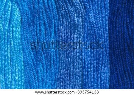 Bright blue range of colors thread floss for embroidery and needlework. Sewing threads for embroidery close-up. Multicolor sewing threads texture. Mouline.  - stock photo