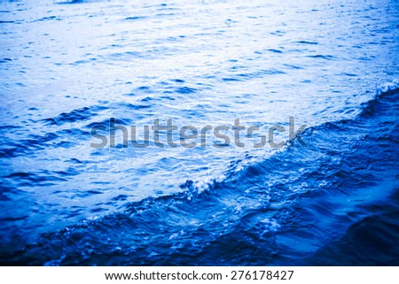 bright blue sea water waves background near coastline in sunset light