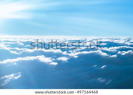 Bright blue sky with clouds and sunlight seen through an airplane window