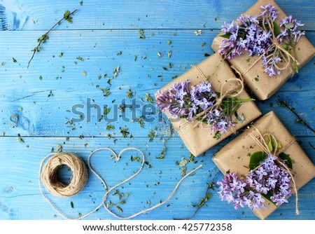 Bright blue wooden background with small gift boxes wrapped with simple brown paper and decorated with natural lilac. Floral decor elements. Copy space - stock photo