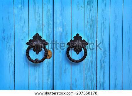 Bright blue wooden door with round handles - stock photo