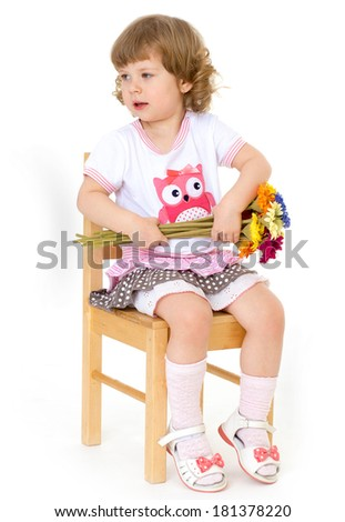 Bright bouquet of spring flowers in the hands of a charming little girl who is sitting on a wooden chair and fun ulybaetsya. Isolated on white background.
