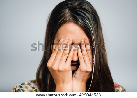 bright brunette girl closes tired eyes with her hands, isolated on a gray background, healthcare concept