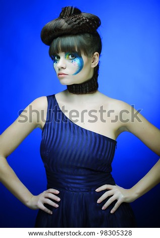 Bright brunette with creative make up in blue dress