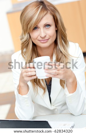 Bright businesswoman holding a cup of coffee in front of her laptop at work