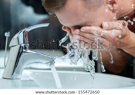 Bright caucasian man spraying water on his face after shaving in the bathroom at home