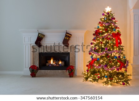 Bright Christmas tree and glowing fireplace in living room.